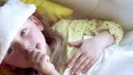 Little girl lying sick in her bed.