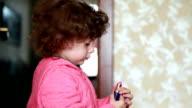 Little girl opening a lipstick