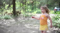 MS PAN Little girl performs for herself outside in woods camping / Toronto, Ontario, Canada