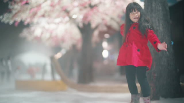 Little girl playing snow with cherry blossom tree background