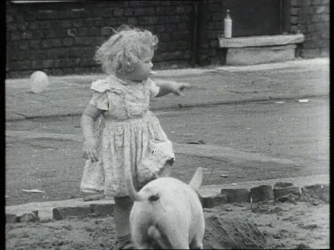 A little girl plays in the mud with a English Bull terrier