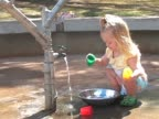Little girl plays in the water filling cups