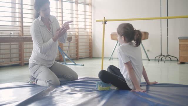 4K: liten flicka tränar höjdhopp inomhus.
