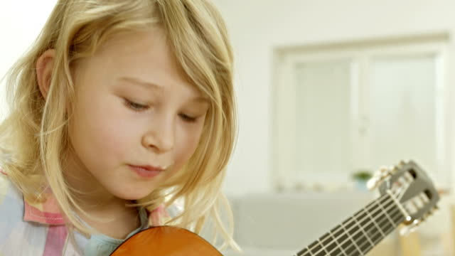 Little Girl Practicing Playing The Guitar