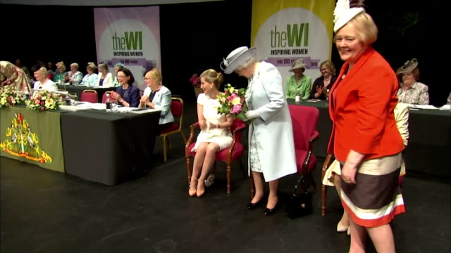 A little girl presents Queen Elizabeth II with a bouquet The Queen opened the centenary annual meeting of the Women's Institute at the Royal Albert...