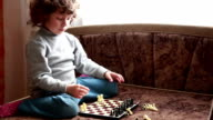 Little girl putting chess pieces on the chessboard