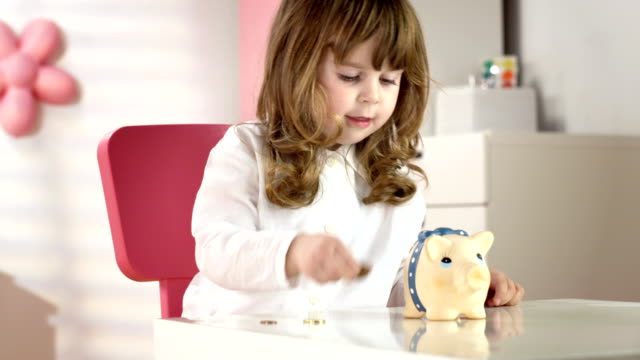 HD DOLLY: Little Girl Putting Coins Into A Piggy Bank