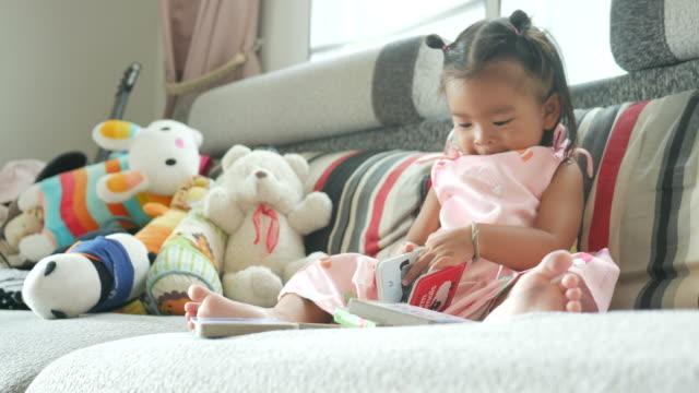 little girl reading book in living room