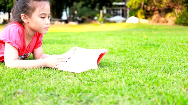 Little girl reading book on green grass.
