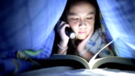 Little girl reading book under the blanket