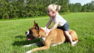 Little girl rides her dog
