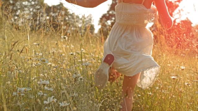 SLO MO TS Little girl running in high grass towards the sun