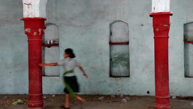 Kleines Mädchen läuft in der Nähe von Säule