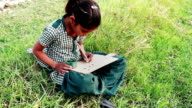 Little Girl Sitting in the Field and Studying Outdoor Portrait