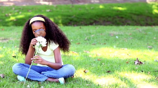 Little girl sitting on grass inspecting a flower