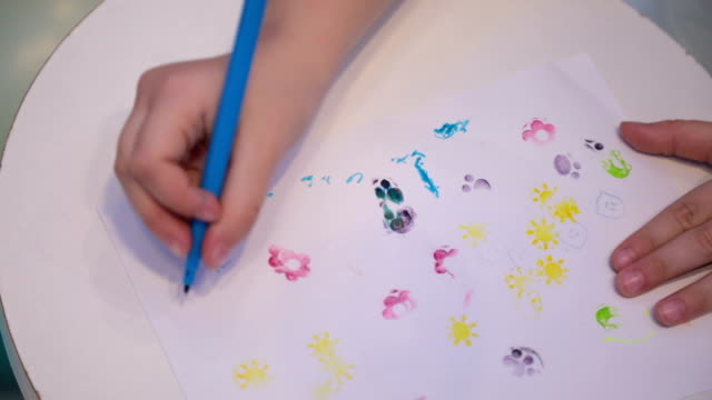 Little Girl Sketching and Drawing in a Preschool Classroom