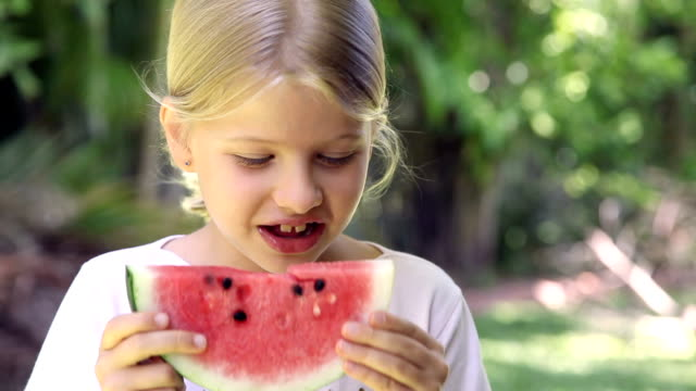 Little girl smiling and eating watermelon fruit outdoors