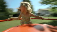 HD: Little Girl Spinning On Playground Merry-Go-Round