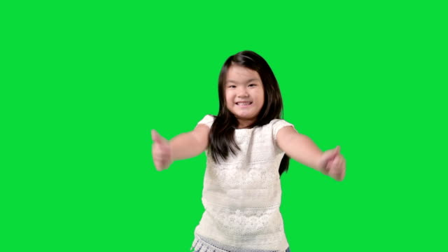 little girl standing in the studio while smiling at the camera and showing thumbs up