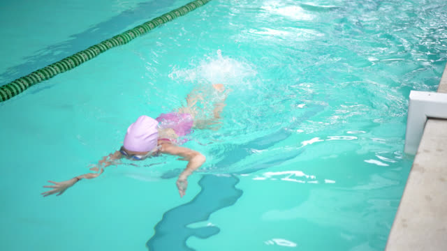 Little girl swimming free style at the pool