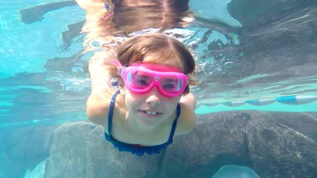 Little Girl Swimming Underwater in Swimming pool