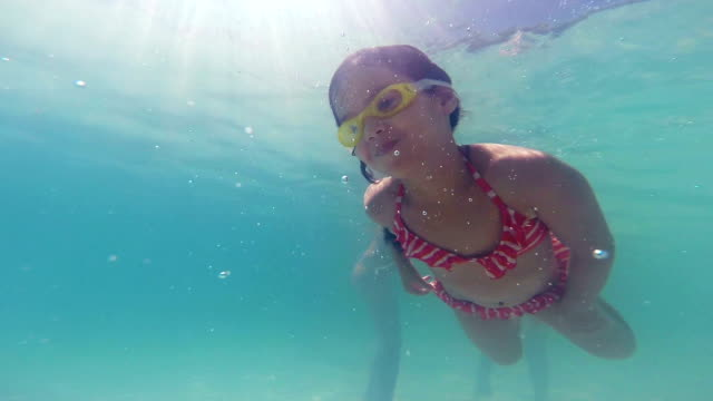 Little Girl Swims Underwater Reaching to Dad's Hand