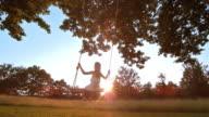 SLO MO meisje swingen bij zonsondergang