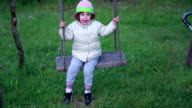 Little girl swings on the rope swing in the backyard