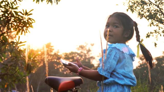Kleines Mädchen mit Handy im Park.