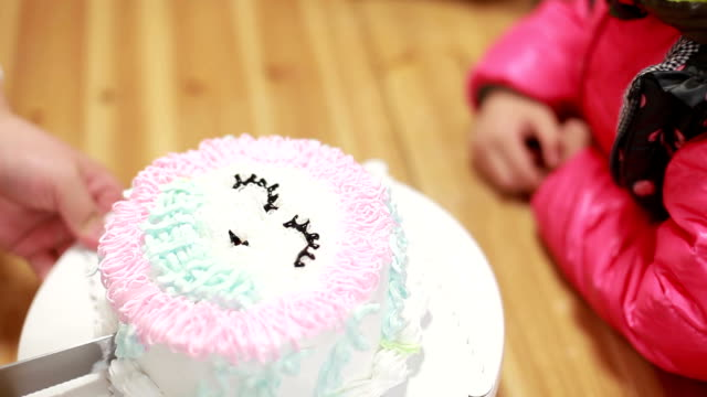 little girl wait the birthday cake to be cut into pieces.
