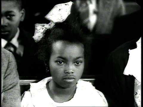 1939 CU little girl wearing large bow in her hair sitting in church pew, other children behind her / USA