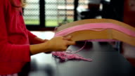 Little girl winding wool on a cardboard to make a huge pompon