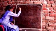 Little girl writing on blackboard