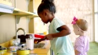 Little girls participate in creative play in a toy kitchen
