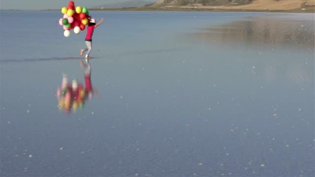 Kleine meisjes lopen op het water met kleur ballonnen SLOWMOTION