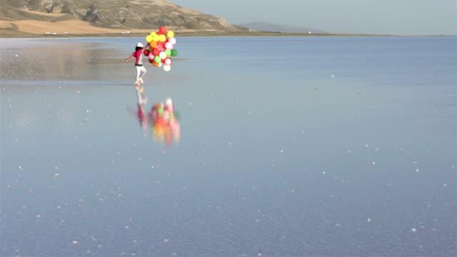 Kleine meisjes lopen op het water met kleur ballonnen