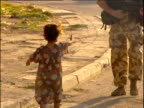 Little Iraqi girl shakes hands with British armed soldier on street patrol Iraq 2004