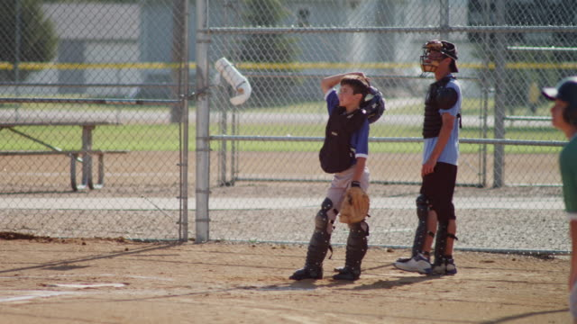 Little league baseball practice in a small town. Shot features a batter at the plate and a catcher. Several pitches come over the plate.