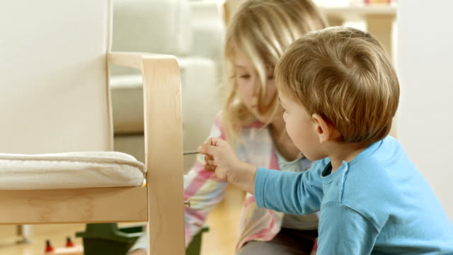 Little Siblings Playing With Repairing A Chair