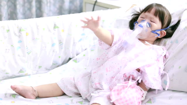 Little sick girl with oxygen mask
