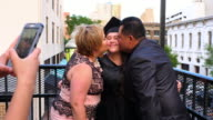 MS TS Little sister taking photo with smartphone of parents kissing graduating daughter during family celebration