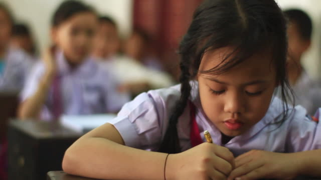 CU SLO MO Little sitting in class and  writing / Vientiane, Laos