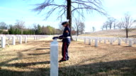 Little Soldier Laying Flag On Grave