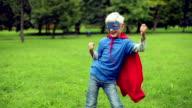 Kleiner Superheld Tanzen im park.