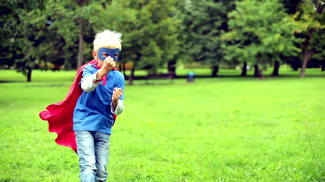Little Superhero fighting in the park.