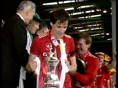 Liverpool fans cheer as captain Alan Hansen raises trophy player manager Kenny Dalglish and rest of team follow down steps Everton vs Liverpool 1986...