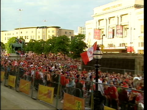 Liverpool FC return after Champions League victory airport arrival/ parade Banner hanging from window PULL OUT to GV mass fans gathered TGVs Mass...