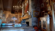 WS DS living room in rustic, mid-century lodge with natural stone fireplace, wood-paneled walls, cathedral ceiling and California art on all walls