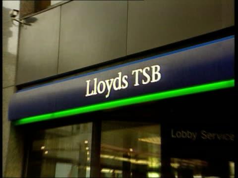 Lloyds TSB launches bid for Abbey National LIB London Branch of Lloyds TSB bank ZOOM IN sign SIDE MS Men using cash dispensers TILT UP sign GV...
