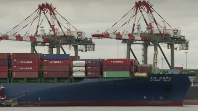 A loaded container ship heads out to sea from the Port of Newark taken from Bayonne.  Large cranes sit behind